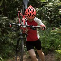 Young Female Cyclist With mountain bike on mountain trail